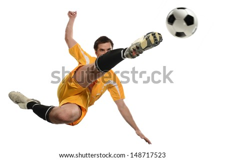 Soccer player kicking ball while jumping isolated over white background