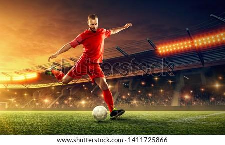 Soccer player kicks a ball. Action. Sports event. Night soccer stadium