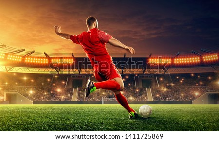 Soccer player kicks a ball. Action. Sports event. Night soccer stadium
