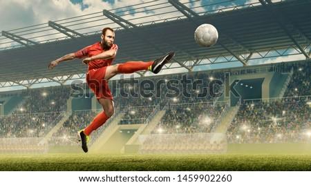Soccer player kicks a ball. Floodlit soccer stadium with crowded tribunes