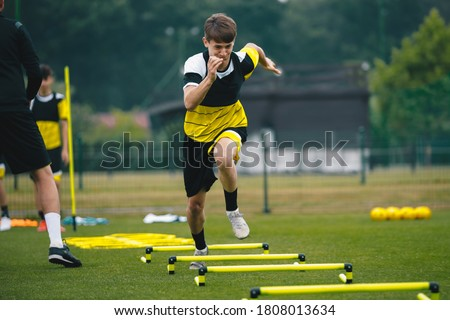 Soccer player running fast and ladder skipping. Teenagers on soccer training camp. Boys practice football witch young coach. Junior level athletes improving soccer skills on outdoor training