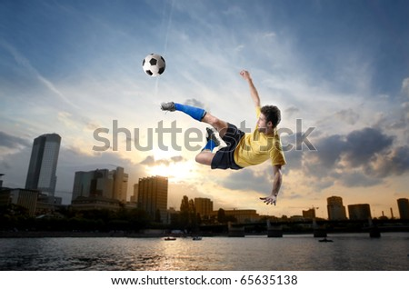 Soccer player shooting a football with cityscape on the background