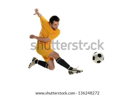 Soccer player wearing a yellow uniform kicking the ball on a white background