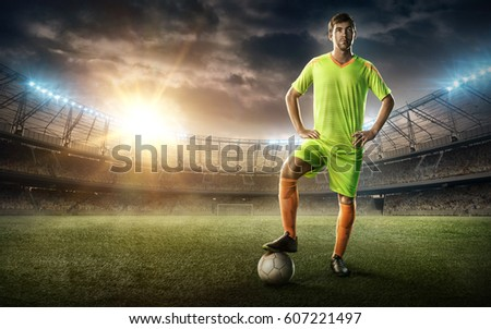 soccer player with a ball on a soccer stadium with tribunes on sunset