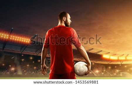 Soccer player with a ball stands in front of cheering fans on the stadium. View from back. Floodlit soccer stadium with dramatic sky.