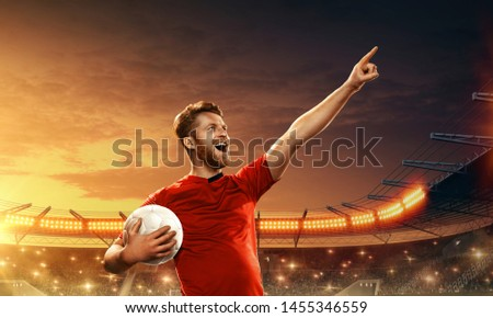 Soccer player with ball on a floodlit night stadium celebrates scored goal #1455346559