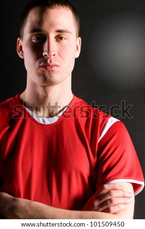 soccer player with folded hands on dark background