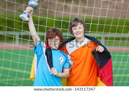 soccer player with trophy and german flag standing in goal