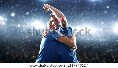 Soccer players are celebrating a victory on the professional stadium while it's snowing. Stadium and crowd are made in 3D.