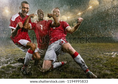 Soccer players on professional soccer night rain stadium. Three dirty players in rain drops emotionally rejoices victory. Men kneel and scream #1194995833