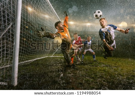 Soccer players performs an action play on a professional night rain stadium. Dirty player in rain drops scores a goal with head. Goalkeeper in flight trying to catch the ball. Grass in the stadium wet #1194988054