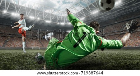 Soccer players performs an action play on a professional stadium. The football goalkeeper catches the ball. All players wear unbranded clothes. The stadium is made in 3D.
