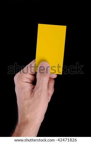 Soccer referee awarding yellow card, hand isolated on black background