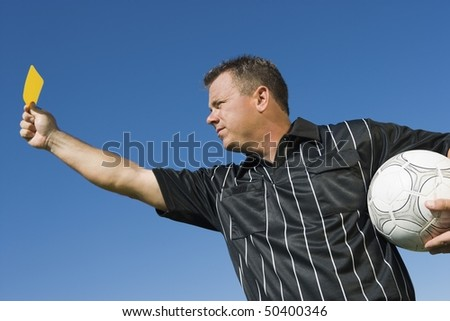 Soccer referee holding yellow card, portrait