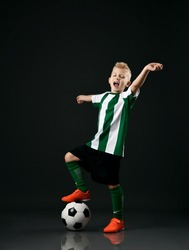 Soccer school student, boy in red white uniform stands with ball under his foot, holds arms outstretched and yawn or sings over black background
