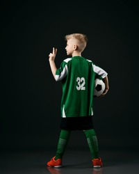 Soccer school student, teenager boy in red white striped uniform stands back to camera holding ball and gesturing V sign over black background. Back view