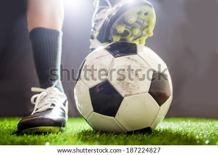 Soccer shoes & football on the green grass
