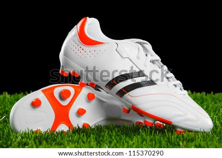 Soccer shoes on the green grass. Closeup