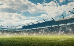 Soccer stadium with tribunes and illumination. Green grass and cloudy blue sky.