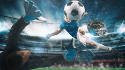 Soccer striker hits the ball with an acrobatic kick in the air at the stadium at night match