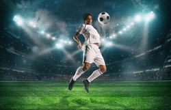 Soccer striker stops the ball with an acrobatic jump at the stadium during a night match
