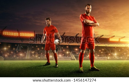 Soccer team in red uniform on a floodlit night stadium with spectators.