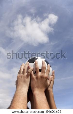 Soccer team raising a ball to the sky