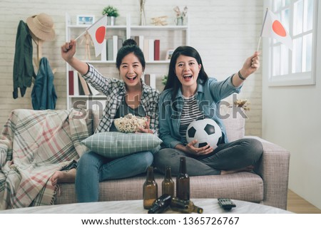 Soccer women fans emotionally watching football game on television in living room. cheerful girls friends with japan flag cheer up on games sitting in couch sofa. happy female eat popcorn with beers #1365726767