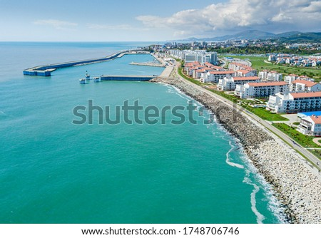 Photo of  Sochi cityscape and Black sea shore from aerial view. Adler district from above. Resort town in the Caucasus mountains.