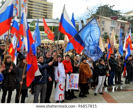 SOCHI, RUSSIA - MARCH 05: Peoples hold posters and headers with slogans in support of Vladimir Putin on presidential elections of the Russian Federation on March 05, 2012 in Sochi. - stock photo