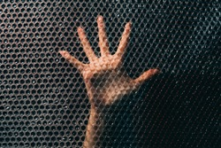Social anxiety. Panic attack. Nervous breakdown. Fear tense. Desperate insecure woman hand trying to find way out trapped behind plastic bubble wrap textured wall in darkness.