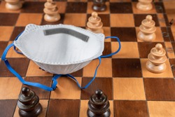 Social control and social distancing concept in the 2019-ncov or coronavirus crisis. A medical mask on a chessboard with several pawns respecting the safety distance