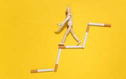 Social degradation due to bad habits. Wooden puppet steps down the stairs of cigarettes on a yellow background
