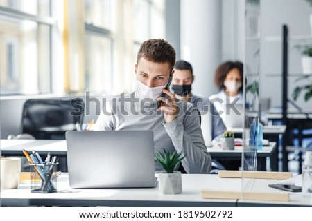 Social distance and online work with client remotely. Busy man in protective mask talking on smart phone sitting at office in workplace with laptop and glass board during coronavirus, copy space
