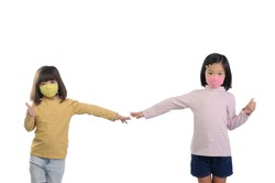 Social distance concept. Two Asian kids showing thumbs up gesture ,wearing mask standing distance of 1 meter from other people keep distance protect from COVID-19 and The risk of infection to others.
