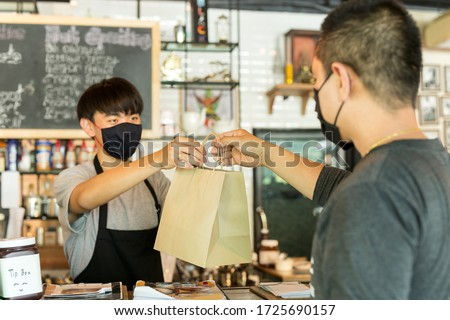 Social distance conceptual waiter giving takeaway bag to customer at cafe.