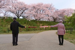 Social distancing. A good example of social distancing to avoid the spread of coronavirus (COVID-19). Two people (a man and a woman) stand apart holding two umbrellas.