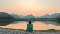 Social distancing, a woman is sitting alone by the lake during sunset moment.