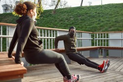 Social distancing. African couple in protective masks working out in park outdoors. Doing push-ups exercises on bench, training triceps. Sport in quarantine. Covid-19. Protection