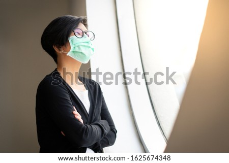 Social distancing, Asian woman stand by window, look out, wear medical face mask, protect from infection of Covid-19 virus, pandemic, outbreak and epidemic of disease in quiet quarantined city.