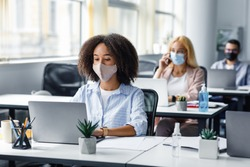 Social distancing at coronavirus outbreak situation. Pretty african american lady in protective mask typing on laptop, working for company support center in office interior with other employees