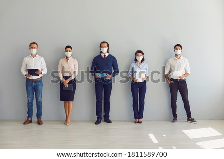 Social Distancing at Work concept. Office workers or job candidates in protective face masks standing in corridor. Applicants waiting for interview keeping safe distance to prevent spread of Covid 19