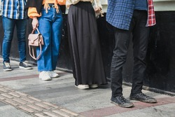Social distancing concept with people in queue. Unrecognizable faces, close up on the feet of young people respecting the law disposition for coronavirus pandemic disease
