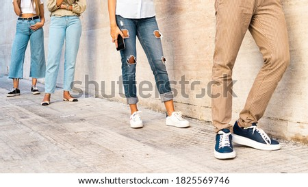 Social distancing concept with people in queue. Unrecognizable faces, closeup on the feet of young people respecting the law disposition for coronavirus pandemic disease. Stock photo ©