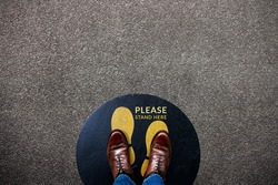 Social Distancing for Covid-19 Situation Concept. Signage for Cooperate in Public Place on the Floor. Person Standing  inside a Stand Notice Sign