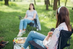 Social distancing. Girls Friends chilling among trees at picnic with social distance in summer park. Leisure activity together in new normal, safety gatherings. Young woman relaxing