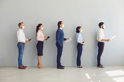 Social Distancing in Office concept. Company employees or job applicants in face masks standing in corridor. Candidates waiting for interview keeping safe distance to prevent spread of coronavirus