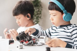 Social distancing & Learning activities, Two Asian brothers boys with headphone assemble and test a robot with EV3 components as school project at home due to school closed and Covid-19 pandemic