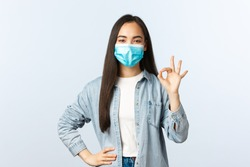Social distancing lifestyle, covid-19 pandemic everyday life concept. Satisfied confident asian girl have all under control, guarantee and encourage everything good with okay sign, wear mask