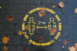 Social distancing sign painted on wet sidewalk, wet autumn leaves on the ground